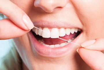flossing teeth after gum disease and bone disease therapy in austin