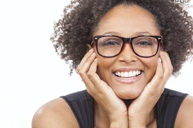 woman with glasses holding her face smiling